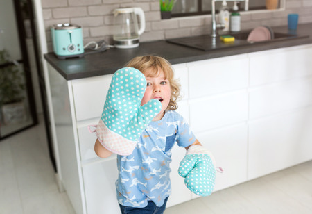 Boy playing in the kitchen with protective gloves on his hands