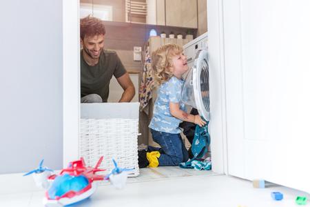 Father and son loading washing machine Stockfoto