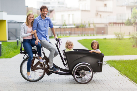 Young family having a ride with cargo bike