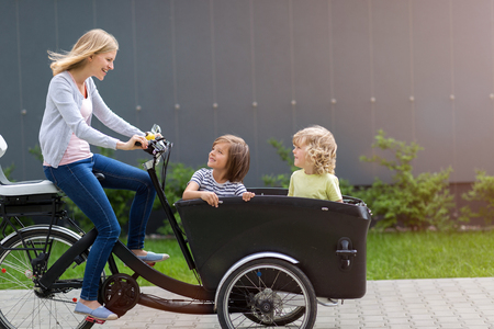 Mother and children having a ride with cargo bike