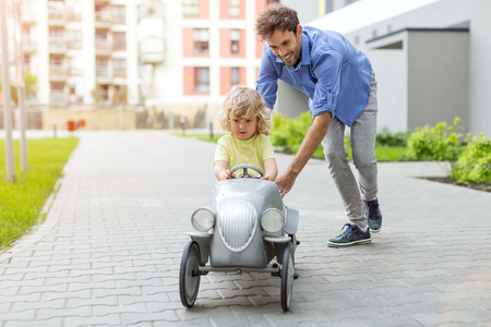 Father helping his son to drive a toy peddle car Stock Photo