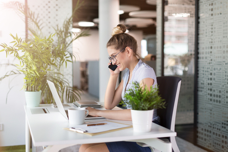 Young business woman talking on the phone in office Stockfoto
