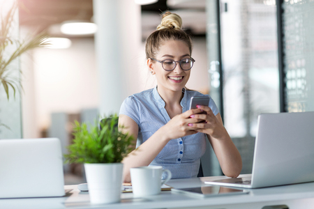 Business woman using smart phone in office
