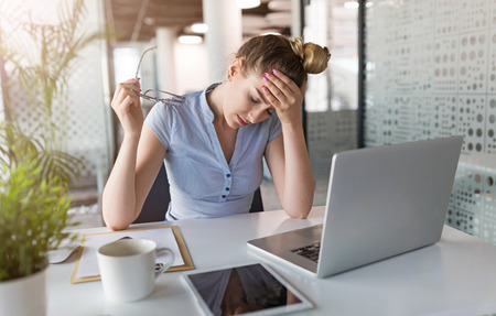 Tired, stressed businesswoman at laptop in office Stockfoto