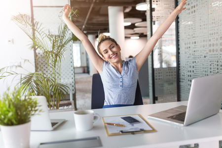 Businesswoman With Laptop Celebrating Success At Office Desk