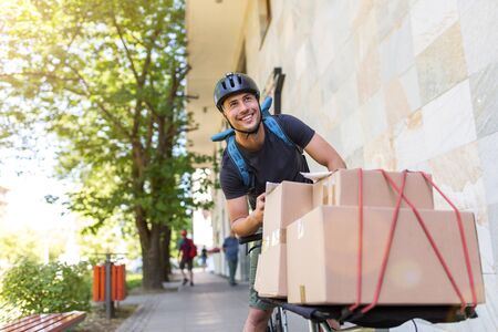 Bicycle messenger making a delivery on a cargo bike 免版税图像