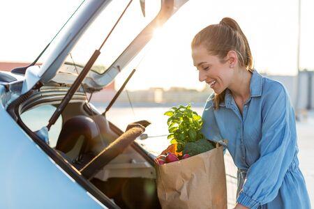 Giovane donna nel parcheggio, caricamento della spesa nel bagagliaio dell'auto