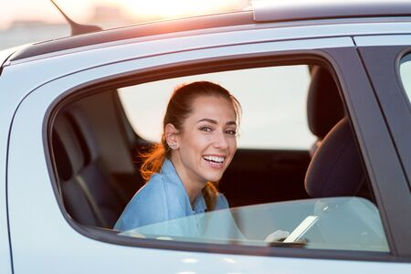 Young woman with smartphone on the back seat of a car Zdjęcie Seryjne - 125165049