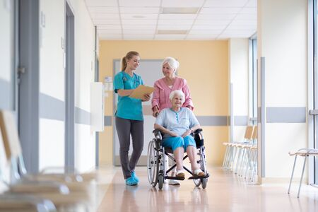 Senior woman in wheelchair with nurse in hospital Stock fotó