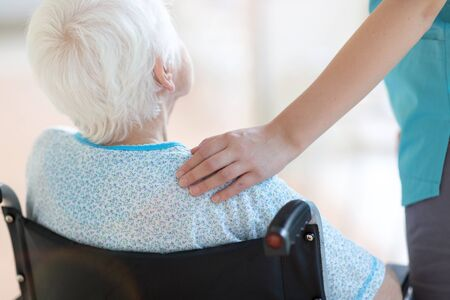 Senior woman in wheelchair with nurse in hospital 免版税图像