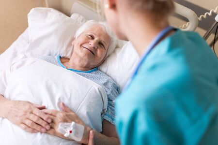 Senior female patient in hospital bed