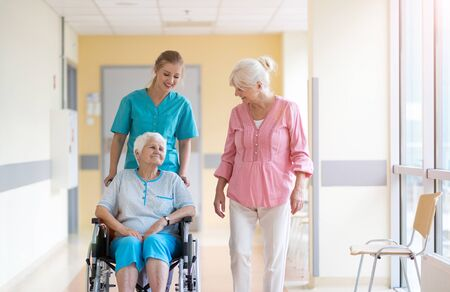 Elderly woman on wheelchair with her daughter and nurse