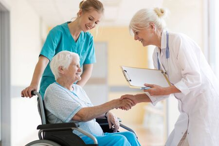 Senior woman in wheelchair with doctor in hospital Stock Photo