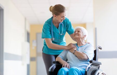 Senior woman in wheelchair with nurse in hospital Stock Photo