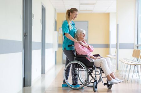 Senior woman in wheelchair with nurse in hospital Standard-Bild