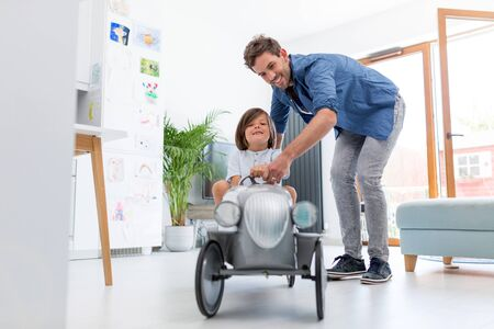 Father helping his son to drive a toy peddle car Banco de Imagens