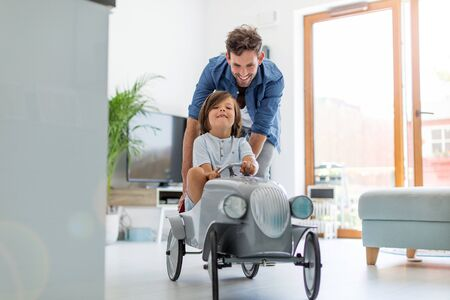 Father helping his son to drive a toy peddle car Stock fotó