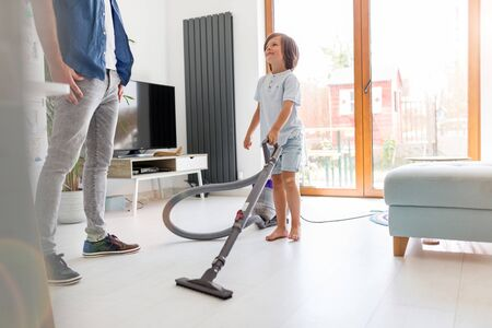 Boy vacuuming floor while father standing at home
