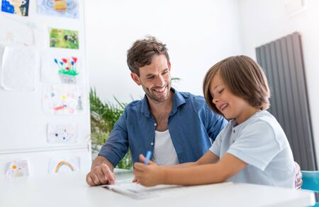 Father and son doing homework together at home Banco de Imagens