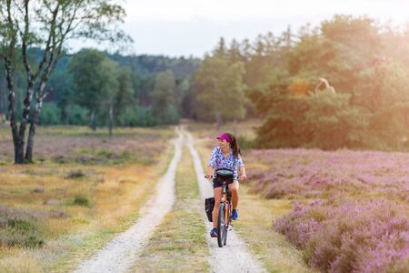Young woman riding bicycle in the countryside, Hoge Veluwe, Holland