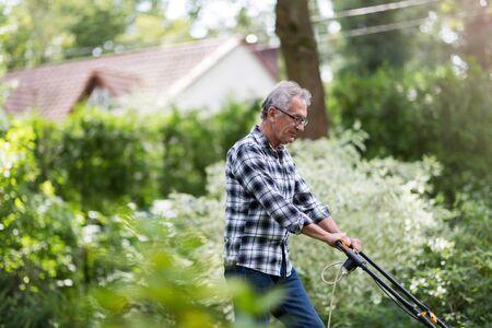 Elderly man mowing the lawn