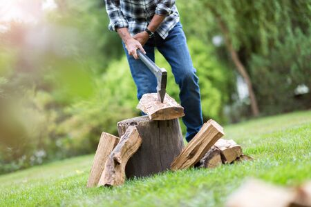 Senior man cutting logs, working in the garden (focus on ax)