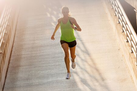 Young woman jogging in urban area at sunset