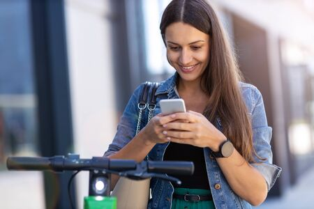 Young woman with electric scooter checking her smartphone Stock fotó
