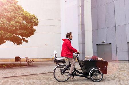 Junger Mann, der mit einem Lastenfahrrad vom Einkaufen zurückkehrt Standard-Bild