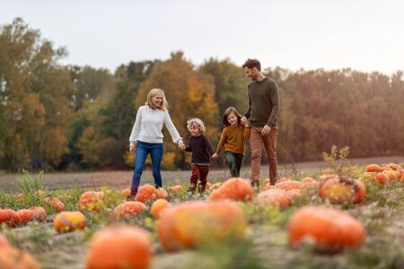Happy young family in pumpkin patch field Stockfoto - 132597326