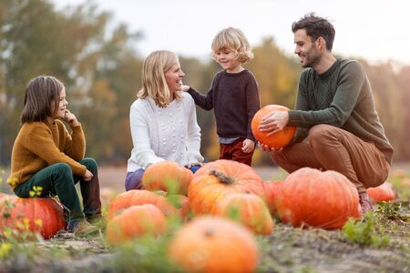 Glückliche junge Familie im Kürbisfleckenfeld