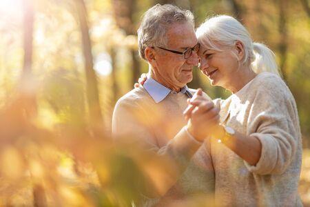 Pareja de ancianos de pie juntos en el parque otoño