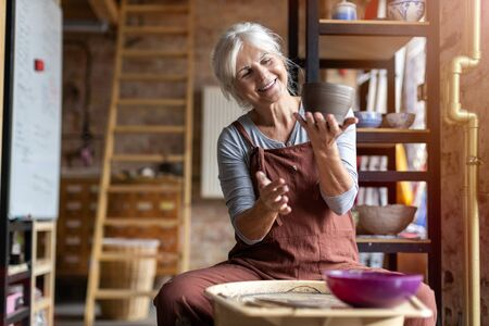 Elderly woman making ceramic work with potter's wheel