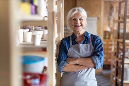 Portrait of senior female pottery artist in her art studio