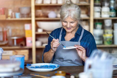 Mature craftswoman painting a plate made of clay in art studio
