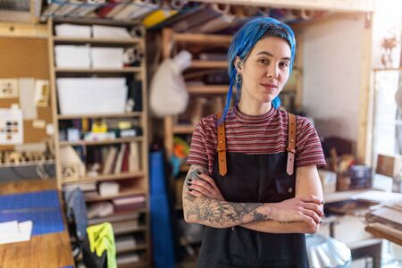 Confident young craftswoman in her workshop
