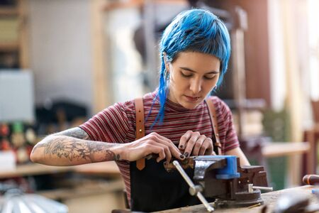 Young woman doing woodwork in a workshop