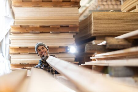 Young man working at a timber warehouse