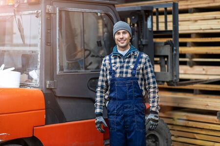 Young male worker standing next to the forklift in lumber yard Stock fotó