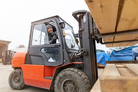 Young male worker driving forklift in lumber yard