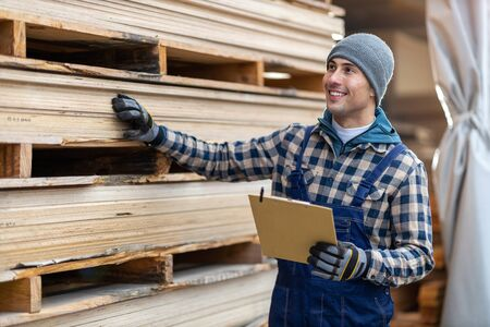 Young male worker in timber warehouse Stock fotó