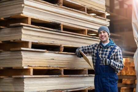 Young male worker in timber warehouse Banco de Imagens