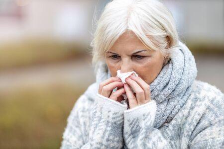 Femme âgée malade se mouchant Banque d'images