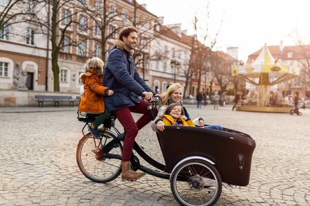Young family enjoying spending time together, riding in a cargo bicycle