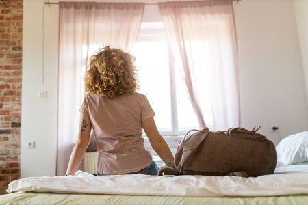 Rear view of woman sitting on bed in youth hostel
