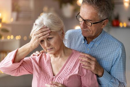 Senior man consoling his suffering wife at home Foto de archivo