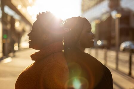 Two beautiful Afro american women standing back to back in city Stock Photo