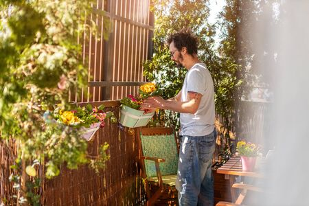 Young man taking care of his plants on the balcony