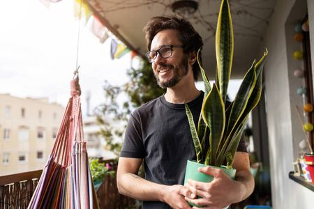 Young man taking care of his plants on a balcony