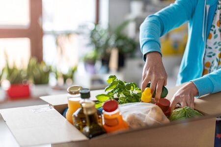 Young woman unpacking boxes of food at home